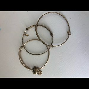 Set of 3 Alex and Ani gold bangles.